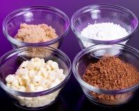 Συστατικά ψησίματος - άσπρα τσιπ σοκολάτας, καφετιά ζάχαρη, κονιοποιημένα ζάχαρη και κακάο που κονιοποιούνται Στοκ Φωτογραφίες