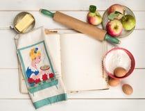 Συστατικά ψησίματος πιτών της Apple με την κενή σελίδα βιβλίων συνταγής, την κυλώντας καρφίτσα, την εκλεκτής ποιότητας πετσέτα κο Στοκ φωτογραφία με δικαίωμα ελεύθερης χρήσης
