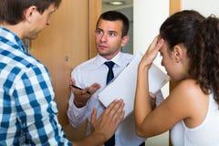 Συλλέκτης και ζεύγος χρέους στην πόρτα στοκ εικόνες