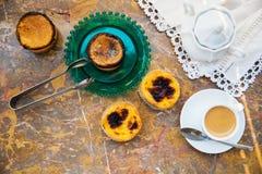 Συλλήφθείτε με τον καφέ πρωινού και τα κέικ & x28 Pasteis de nata, χαρακτηριστική ζύμη από Portugal& x29  στη φυσική μαρμάρινη επ Στοκ Φωτογραφία