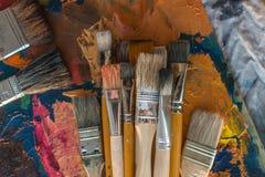 Συλλογή πινέλων στην παλαιά τοπ άποψη παλετών Μίξη των διαφορετικών ελαιοχρωμάτων στο στούντιο τέχνης στοκ φωτογραφία με δικαίωμα ελεύθερης χρήσης