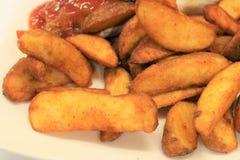 Σφήνες πατατών Χρυσές τηγανισμένες τραγανές σφήνες πατατών Στοκ Φωτογραφία