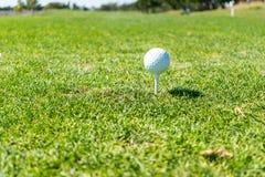 Σφαίρα γκολφ έτοιμη να τοποθετήσει στο σημείο αφετηρίας μακριά πάνω από το γράμμα Τ στο γήπεδο του γκολφ Στοκ Φωτογραφία