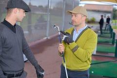 Σφαίρα γκολφ κατάρτισης με τον κάδο στην τραχιά χλόη Στοκ Εικόνες