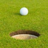 Σφαίρα γκολφ μπροστά από την τρύπα, εστίαση στην τρύπα Στοκ Εικόνες