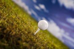 Σφαίρα γκολφ στην πράσινη χλόη πέρα από έναν μπλε ουρανό Στοκ Φωτογραφία