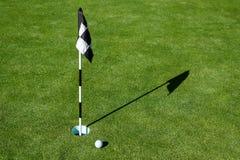Σφαίρα γκολφ στην τοποθέτηση πρακτικής πράσινη δίπλα στην τρύπα και τη σημαία, ηλιόλουστο πρωί στοκ εικόνα