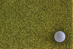 Σφαίρα γκολφ στο πράσινο πίσω έδαφος στοκ εικόνες