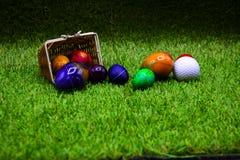 Σφαίρα γκολφ με τα αυγά Πάσχας στην πράσινη χλόη Στοκ Φωτογραφίες