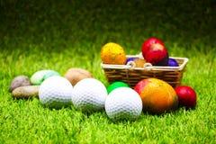 Σφαίρα γκολφ με τα αυγά Πάσχας στην πράσινη χλόη Στοκ εικόνα με δικαίωμα ελεύθερης χρήσης
