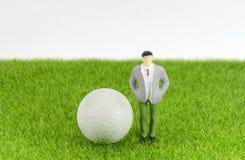Σφαίρα γκολφ με το μίνι επιχειρηματία παιχνιδιών σε μια χλόη Στοκ Εικόνες