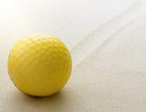 Σφαίρα γκολφ Yllow στην άμμο Στοκ Εικόνες