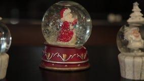 Σφαίρα γυαλιού με το παιχνίδι Άγιος Βασίλης μέσα απόθεμα βίντεο