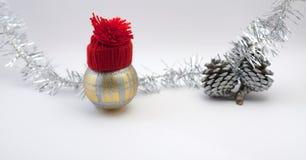 Σφαίρα διακοσμήσεων Χριστουγέννων με το κόκκινο χειροποίητο κόκκινο καπέλο Στοκ φωτογραφία με δικαίωμα ελεύθερης χρήσης