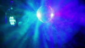 Σφαίρα καθρεφτών για το disco σε ένα μαύρο υπόβαθρο στις ακτίνες από τα επίκεντρα και τα σύννεφα του χρωματισμένου καπνού απόθεμα βίντεο