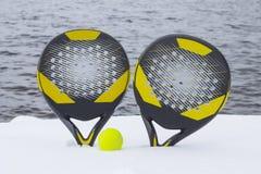 Σφαίρα και δύο ρακέτες αντισφαίρισης παραλιών στη χιονισμένη παραλία στα πλαίσια της θάλασσας στοκ εικόνες