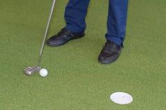 Σφαίρα και τρύπα γκολφ λεσχών στο εσωτερικό γήπεδο του γκολφ Στοκ Φωτογραφία