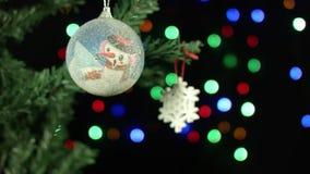 Σφαίρα και χιόνι διακοσμήσεων Χριστουγέννων στο δέντρο στο υπόβαθρο των θολωμένων γιρλαντών φω'των απόθεμα βίντεο