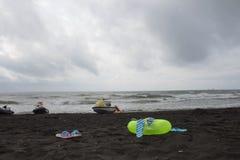 Σφαίρα, κολυμπώντας γυαλιά, σανδάλι, μηχανικό δίκυκλο νερού και επιπλέον δαχτυλίδι στην παραλία συννεφιασμένος, κύμα στοκ εικόνα