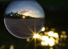 Σφαίρα κρυστάλλου με τη φλόγα, bokeh και το ηλιοβασίλεμα ήλιων Στοκ Εικόνες
