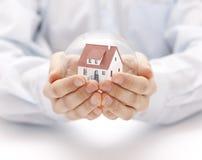 Σφαίρα κρυστάλλου με το σπίτι στα χέρια Στοκ Φωτογραφίες