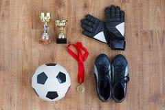 Σφαίρα, μπότες ποδοσφαίρου, γάντια, φλυτζάνια και μετάλλιο Στοκ φωτογραφία με δικαίωμα ελεύθερης χρήσης