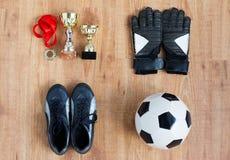 Σφαίρα, μπότες ποδοσφαίρου, γάντια, φλυτζάνια και μετάλλιο Στοκ Φωτογραφίες