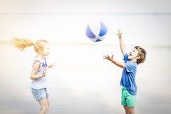Σφαίρα νερού παιχνιδιού κοριτσιών και αγοριών στην παραλία Στοκ φωτογραφία με δικαίωμα ελεύθερης χρήσης