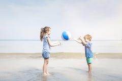 Σφαίρα νερού παιχνιδιού κοριτσιών και αγοριών στην παραλία Στοκ εικόνα με δικαίωμα ελεύθερης χρήσης