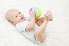 Σφαίρα παιχνιδιών παιχνιδιού μωρών, ευτυχές παιδί που βρίσκεται στην πλάτη που παίζει τα μαλακά παιχνίδια στοκ εικόνες