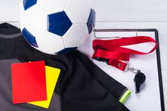 Σφαίρα ποδοσφαίρου, αθλητική μπλούζα, καταγράφοντας ταμπλέτα, δύο κάρτες ποινικής ρήτρας και ένας συριγμός στην κόκκινη κορδέλλα  Στοκ Εικόνα