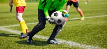 Σφαίρα ποδοσφαίρου εκμετάλλευσης τερματοφυλακάων ποδοσφαίρου Τερματοφύλακας ποδοσφαίρου που πιάνει τις δεξιότητες Στοκ Φωτογραφίες