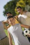 Σφαίρα ποδοσφαίρου εκμετάλλευσης αγοριών (13-15) με τρία άτομα στο πάρκο. Στοκ Φωτογραφία