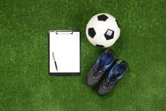 Σφαίρα ποδοσφαίρου, μπότες ποδοσφαίρου, σημειωματάριο ή σημειώσεις και μάνδρα διαγραμμάτων Στοκ Φωτογραφία