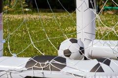 Σφαίρα ποδοσφαίρου παιδιών σε έναν στόχο Στοκ Φωτογραφία