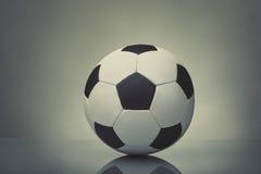 Σφαίρα ποδοσφαίρου στη σκοτεινή ανασκόπηση Στοκ Φωτογραφίες
