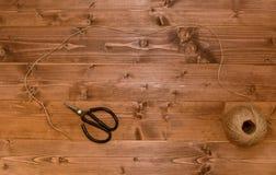 Σφαίρα του σπάγγου που ξετυλίγεται πέρα από ένα ξύλινο υπόβαθρο στοκ εικόνα