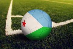 Σφαίρα του Τζιμπουτί στη θέση λακτίσματος γωνιών, υπόβαθρο γηπέδων ποδοσφαίρου Εθνικό θέμα ποδοσφαίρου στην πράσινη χλόη στοκ φωτογραφία με δικαίωμα ελεύθερης χρήσης