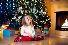 Σφαίρα χιονιού εκμετάλλευσης μικρών κοριτσιών κάτω από το χριστουγεννιάτικο δέντρο Στοκ φωτογραφία με δικαίωμα ελεύθερης χρήσης