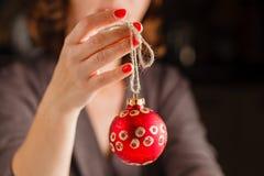 Σφαίρα Χριστουγέννων εκμετάλλευσης κοριτσιών στα δάχτυλα Όμορφο μανικιούρ στο α Στοκ εικόνες με δικαίωμα ελεύθερης χρήσης