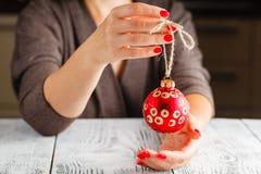 Σφαίρα Χριστουγέννων εκμετάλλευσης κοριτσιών στα δάχτυλα Όμορφο μανικιούρ στο α Στοκ Εικόνες