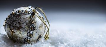 Σφαίρα Χριστουγέννων πολυτέλειας στο χιόνι και τις χιονώδεις αφηρημένες σκηνές στοκ εικόνα με δικαίωμα ελεύθερης χρήσης