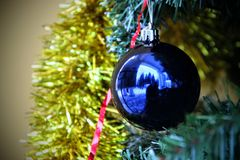 Σφαίρα Χριστουγέννων Σε ένα υπόβαθρο της χρυσής tinsel μπλε σφαίρας στοκ εικόνες