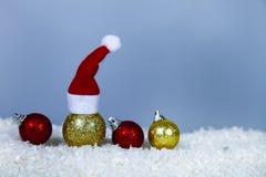 Σφαίρα Χριστουγέννων σε ένα Santa ΚΑΠ και σφαίρες στο χιόνι στοκ εικόνες