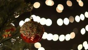 Σφαίρα Χριστουγέννων στον κλάδο έλατου με τα φω'τα bokeh απόθεμα βίντεο