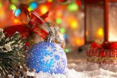 Σφαίρα Χριστουγέννων στο χιόνι, κόκκινο φανάρι με ένα κερί, γιρλάντα των φω'των, bokeh Στοκ Εικόνες