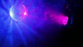 Σφαίρα disco καθρεφτών σε ένα μαύρο υπόβαθρο με τις ακτίνες προβολέων ιριδίζουσες στα διαφορετικά χρώματα σε μια ριπή του καπνού απόθεμα βίντεο