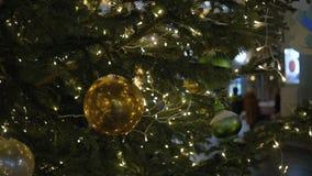 Σφαίρες διακοσμήσεων Χριστουγέννων που κρεμούν στο δέντρο στη γιρλάντα φω'των υποβάθρου Λαμπρή κίτρινη σφαίρα απόθεμα βίντεο