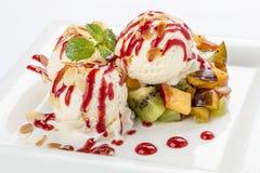 Σφαίρες παγωτού με τα φρούτα σε ένα άσπρο πιάτο στοκ εικόνες