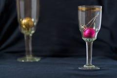 Σφαίρες παιχνιδιών Χριστουγέννων ποτήρια της σαμπάνιας Μαύρη ανασκόπηση Στοκ Φωτογραφίες